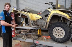 An old and dusty ATV in an expert's garage