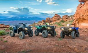 Three ATVs together on a hilly region.