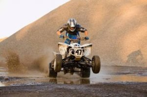 A professional ATV rider driving in a racing manner.