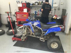An ATV getting fixed in garage