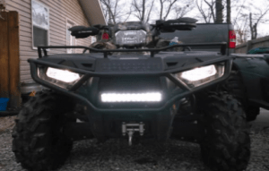 An ATV with a led light bar attached in front for extra lighting