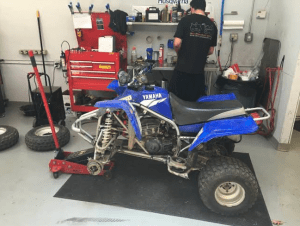 An ATV getting fixed by a professional in the garage