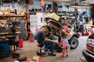 An ATV owner trying to fix his own ATV while the daughter curiously watches.