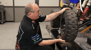 A professional mechanic trying to put the tire back in an ATV