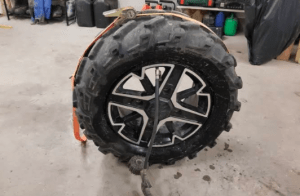 An ATV tire is being repaired in a garage.