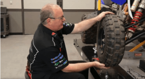 A professional mechanic getting an ATV tire fixed