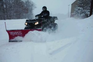 An atv using a customised plow for heavy snow piling.