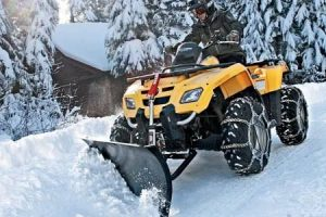 An ATV plow in action with heavy snow.